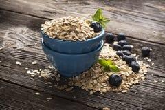 Ciotola ceramica blu in pieno di fiocco di cereali e di giardino fresco del mirtillo delle bacche su un fondo di legno scuro Immagine Stock