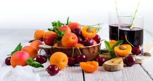 Ciotola ceramica con le ciliege ed il succo maturi organici delle albicocche Immagini Stock Libere da Diritti