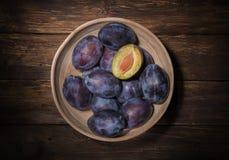 Ciotola ceramica con le prugne sopra il bordo scuro di legno Priorità bassa della frutta Vista superiore Agricoltura, facente il  fotografia stock