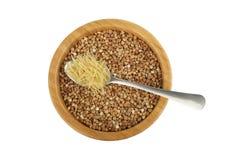 Ciotola con grano saraceno ed il cucchiaio con vermicelli fotografie stock