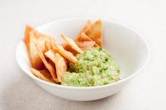 Ciotola con guacamole e nachos fotografie stock