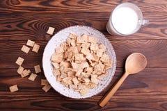 Ciotola con i fiocchi di mais ed il bicchiere di latte immagine stock