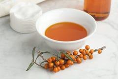 Ciotola con l'olio dell'olivello spinoso Fotografia Stock Libera da Diritti