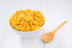 Ciotola dei fiocchi di mais con il cucchiaio su di legno bianco immagine stock
