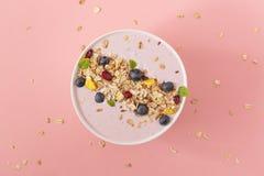 Ciotola del frullato con i melograni, il mirtillo ed il granola su un fondo rosa Prima colazione saporita e sana fotografia stock libera da diritti