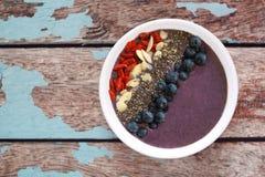 Ciotola del frullato del mirtillo con i superfoods su vecchio legno rustico Fotografie Stock