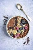 Ciotola del frullato della banana del cioccolato con le bacche ed il granola congelati T Fotografie Stock