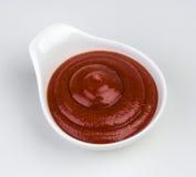 Ciotola del ketchup su fondo bianco Immagine Stock