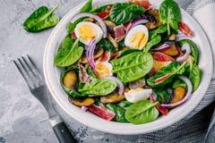 Ciotola del pranzo di insalata degli spinaci con bacon, i funghi, le uova e le cipolle rosse fotografie stock