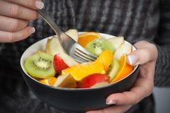 Ciotola della holding della donna di frutta fresca Immagine Stock
