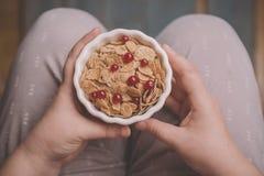 Ciotola della tenuta della donna di fiocchi di mais saporiti del cereale fotografia stock