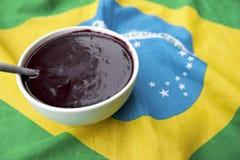 Ciotola di Acai Açaí Jussara sulla bandiera brasiliana Immagine Stock