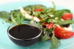 Ciotola di aceto balsamico sul piatto con insalata di verdure immagini stock