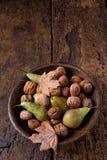 Ciotola di autunno con le pere e le noci Fotografie Stock