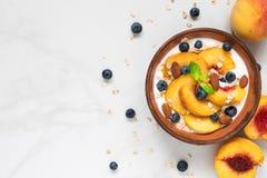Ciotola di avena con yogurt greco, le pesche fresche, i mirtilli e la menta sulla tavola di marmo per la vista superiore della pr immagini stock
