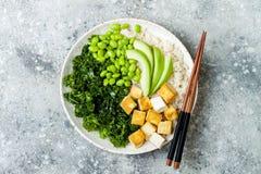 Ciotola di Buddha del riso del cavolfiore con i fagioli massaggiati del cavolo, del tofu, dell'avocado e del edamame Ciotola del  fotografia stock libera da diritti