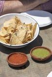 Ciotola di chip di tortiglia con salsa verde e rossa su una tavola Immagine Stock