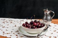 Ciotola di ciliege organiche su un corridore bianco del pizzo Fotografia Stock