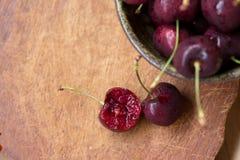Ciotola di ciliege Ciliege rosse in una ciotola su fondo di legno Fotografie Stock Libere da Diritti