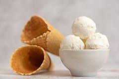 Ciotola di coni della cialda e del gelato alla vaniglia su fondo leggero Vista laterale fotografia stock