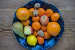 Ciotola di frutta con un fondo di legno Fotografia Stock