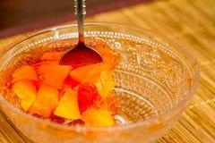 Ciotola di gelatina arancio con frutta variopinta fresca Fotografia Stock