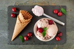 Ciotola di gelato del cioccolato della ciliegia, sopra la scena con i coni sull'ardesia Fotografia Stock