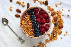Ciotola di granola casalingo con yogurt, le bacche fresche ed il cucchiaio Fotografie Stock Libere da Diritti