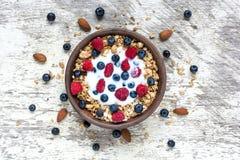 Ciotola di granola dell'avena con yogurt greco, i lamponi freschi, i mirtilli ed i dadi immagini stock