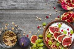 Ciotola di granola dell'avena con yogurt, i semi del melograno, i fichi, l'uva ed i dadi su fondo di legno rustico immagine stock