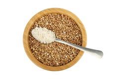 Ciotola di legno con il cucchiaio dell'acciaio e del grano saraceno con riso immagini stock