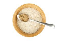 Ciotola di legno con il cucchiaio dell'acciaio e del riso con la lenticchia fotografia stock