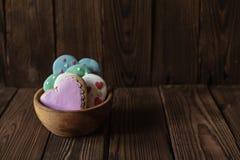 Ciotola di legno con il cuore glased casalingo del pan di zenzero a forma di fotografie stock libere da diritti