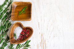 Ciotola di legno con olio d'oliva e le spezie su un fondo bianco Fotografie Stock Libere da Diritti