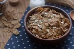 Ciotola di legno di fiocchi di granturco e di farina d'avena organici Prima colazione nutriente, ingredienti alimentari crudi Fotografie Stock