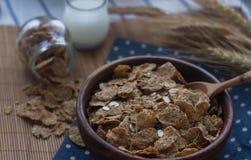 Ciotola di legno di fiocchi di granturco e di farina d'avena organici Prima colazione nutriente, ingredienti alimentari crudi Immagini Stock