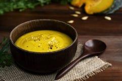 Ciotola di legno di minestra gialla vibrante della zucca con il cucchiaio sulla tavola fotografia stock libera da diritti