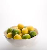 Ciotola di limoni e di limette su bianco. Fotografia Stock