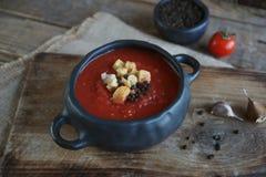 Ciotola di minestra del pomodoro con il chiodo di garofano ed il pepe nero su fondo di legno rustico, fuoco selettivo Fotografia Stock Libera da Diritti