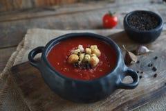 ciotola di minestra del pomodoro con il chiodo di garofano ed il pepe nero sul bordo d'annata e di fondo di legno rustico, fuoco  Fotografie Stock