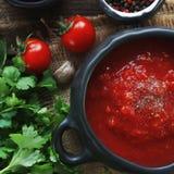 Ciotola di minestra del pomodoro con le erbe fresche, il chiodo di garofano ed il pepe nero su fondo di legno rustico, vista supe Fotografia Stock Libera da Diritti