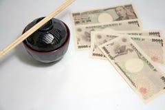 Ciotola di minestra rossa del miso del bordo di colore nero e bastoncini di legno con le banconote di Yen del Giappone sui preced fotografie stock