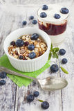 Ciotola di muesli con i mirtilli ed il vetro freschi di yogurt sul whi Fotografie Stock