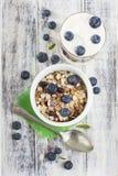 Ciotola di muesli con i mirtilli ed il vetro freschi di yogurt sul whi Immagini Stock