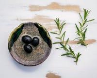 Ciotola di olio d'oliva vergine extra con i rosmarini Ramoscelli dei rosmarini Immagini Stock