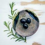 Ciotola di olio d'oliva vergine extra con i rosmarini Ramoscelli dei rosmarini Fotografia Stock
