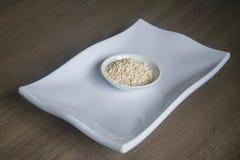 Ciotola di orzo perlato organico sul piatto bianco Fotografia Stock