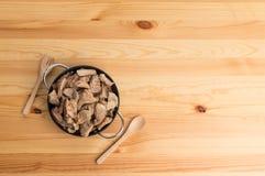 Ciotola di ossequio del cane sulla tavola di legno Immagine Stock