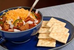 Ciotola di peperoncino rosso e di cracker di spicey con un cucchiaio Immagini Stock