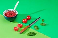 Ciotola di pomodori tagliati sulla tavola verde Immagini Stock